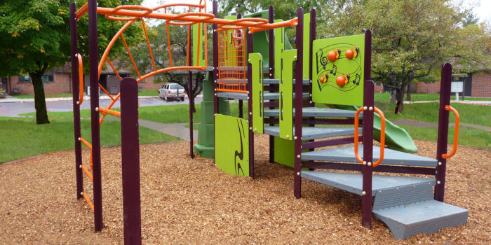 Photo of playground with climbers, a slide, and play panels.