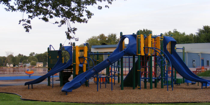 Photo of playground with multiple decks, slides, and climbers.