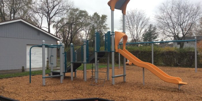 Photo of a play structure with multiple decks, climbers, and a slide.