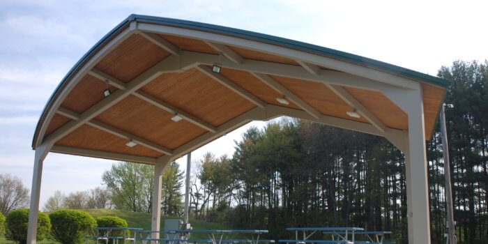 Photo of a large open air pavilion, with a peaked roof and wood ceiling.