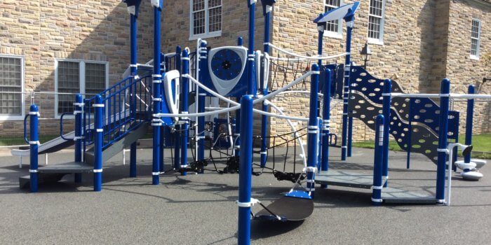 Photo of a playground with climbers, slides, and a rope bridge.