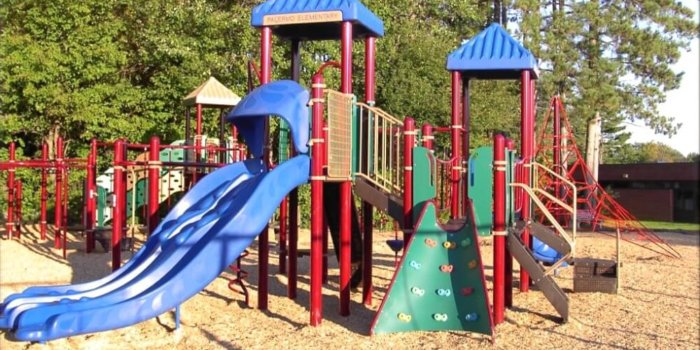 Photo of playground with climbers, slides, overhead play components, and climbing structures.