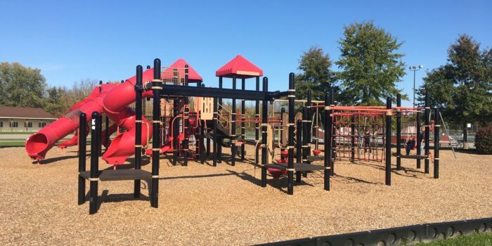Photo of a playground with slides, climbers, decks, and overhead bars.