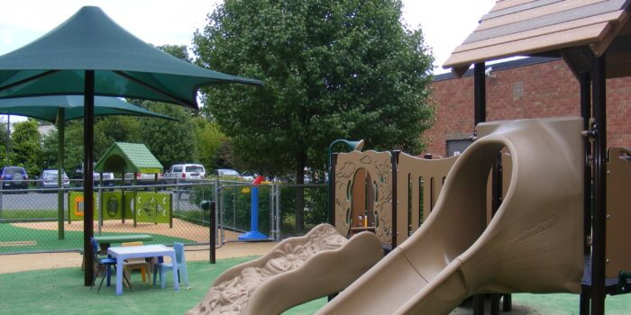 Photo of play structure with slide and climber, with a shade and play panels visible in the background.