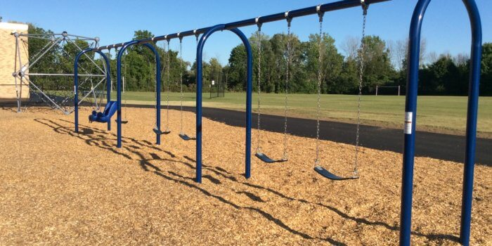 Photo of playground with swings and rope net climbing structure.