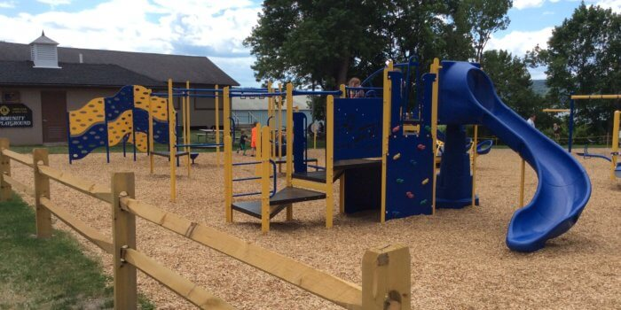 Photo of playground with climbing wall, slide, and independent components.