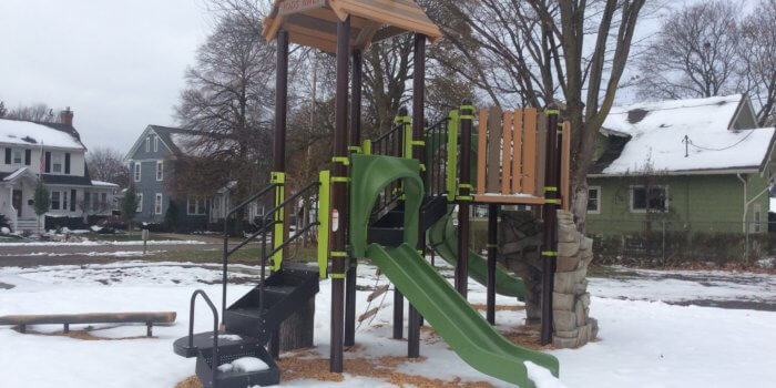 Photo of snow covered nature inspired playground, with a treetop roof, rock shaped climber, and other components.