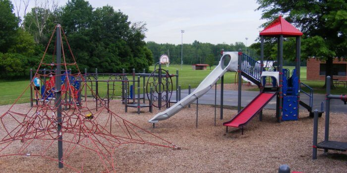 Photo of large cable net climbing structure and two playground structures, one with two slides and climbers and the other with both climbing and overhead play components.