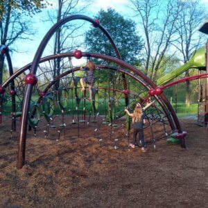 Photo of arched play structure with attached net climber and step bridges