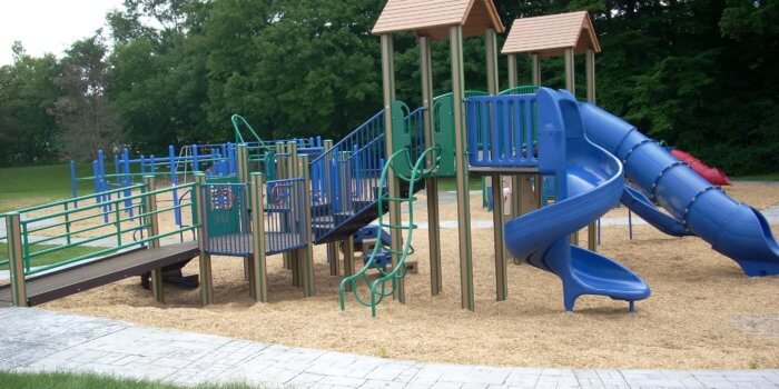 Photo of playground with multiple decks, slides, climbers, and a ramp.