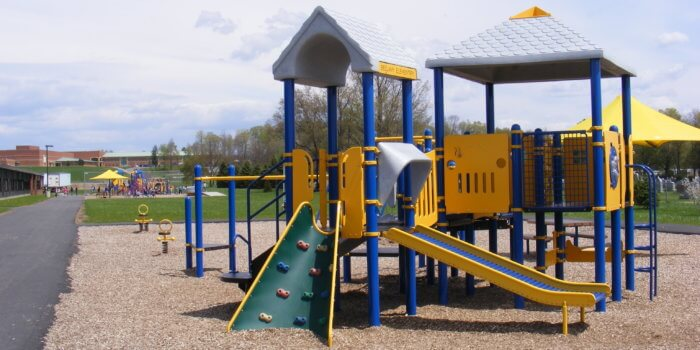 Photo of play structure with decks, climbers, roofs, and roller slide