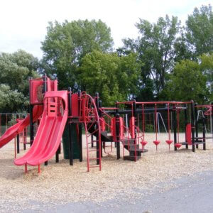 Photo of red and black playground with multiple levels of decks, slides, and climbers
