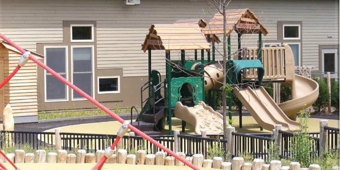 Photo of playground with slides, climbers, and treehouse roofs.