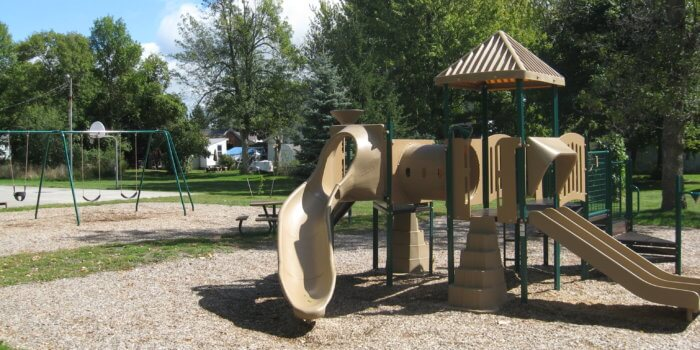Photo of small play structure with slides, play panels, and climbers.