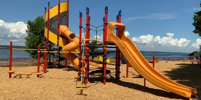 Photo of playground with multi level accessible slide tower, climbers, and other components.