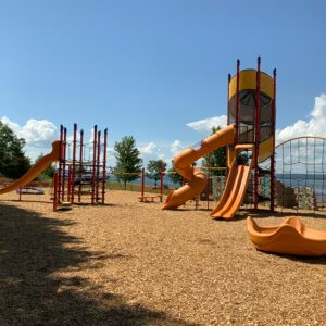 Photo of two large play structures and an independent spinner.