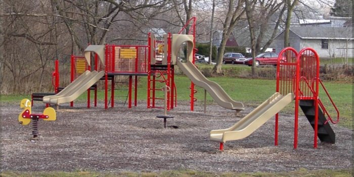 Photo of playground with climbers, slides, spinner, and spring rider.