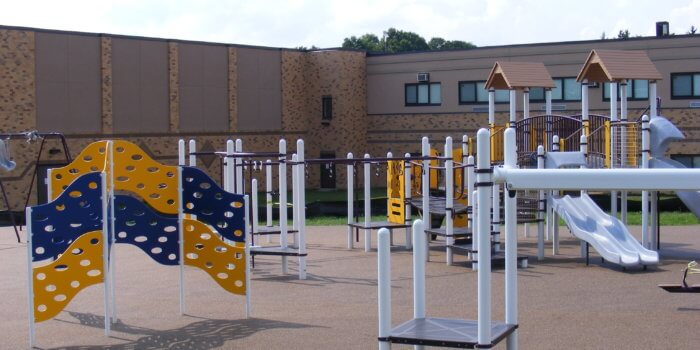 Photo of playground with wavy climbing wall, swingset, zipline, and play structure with climbers and slides.