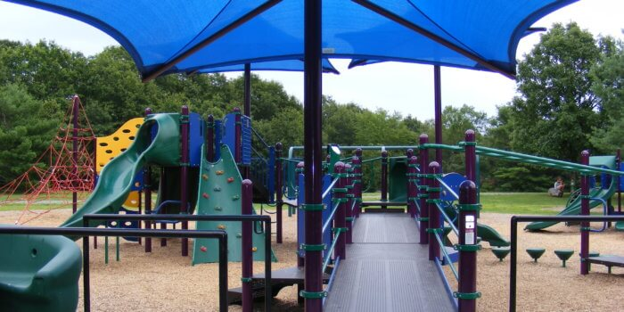 Photo of playground with slides, climbers, an accessible ramp, and a large CoolTopper shade.