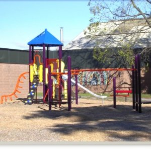 Photo of playground with climbers, slides, and overhead ladder.