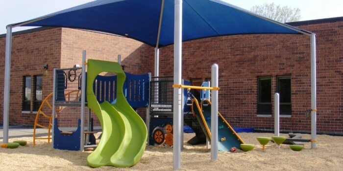 Photo of a small play structure with climbers, play panels, and a slide, with a square shade structure overhead.