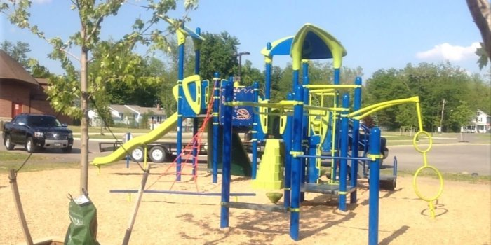 Photo of playground with slides, climbers, spinners, and play panels.