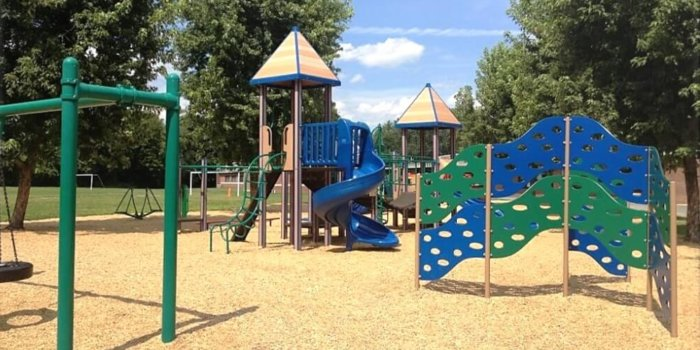 Photo of playground with swings, slides, climbers, and independent components.