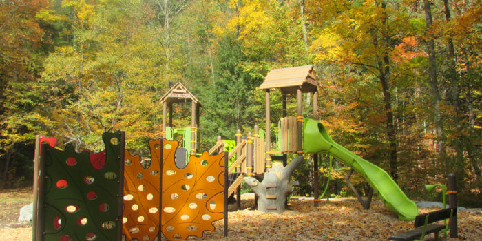Photo of nature-inspired playground with treehouse roofs, tree trunk shaped climbers, and leaf inspired climbing walls, set in a clearing of trees