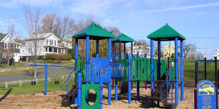Photo of playground with play panels, climbers, and slides.