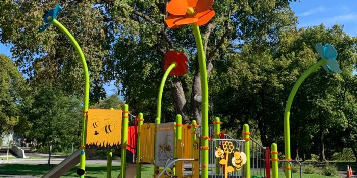 Photo of playground with flower shaped pole toppers, play panels, climbers, and slides.