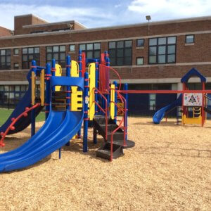 Photo of play structure with slides and climbers in front of a school building.