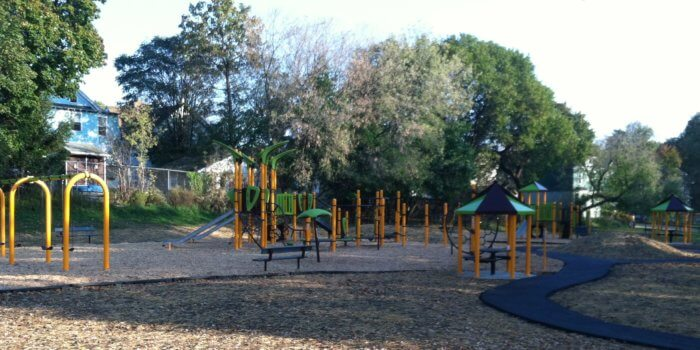 Photo of playground with swings, slides, climbers, and covered picnic tables.