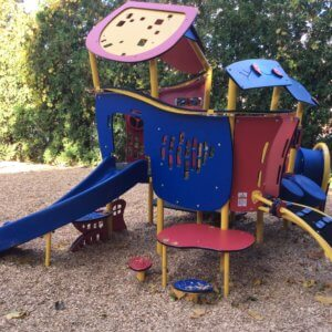 Photo of a small play structure with a slide, climbers, tunnel, play panels, and activity table.