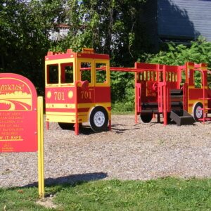 Photo of small custom firetruck-shaped playground, with climbers, play panels, and a slide.