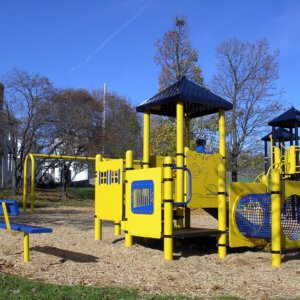 Photo of playground with swings, climbers, tunnels, slides, and play panels.