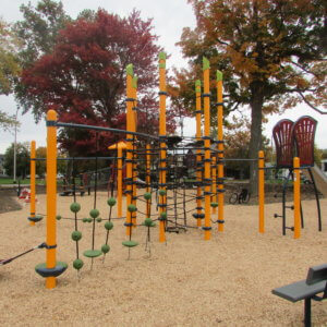 Photo of playground with multi-post net structure, climbers, and slides.