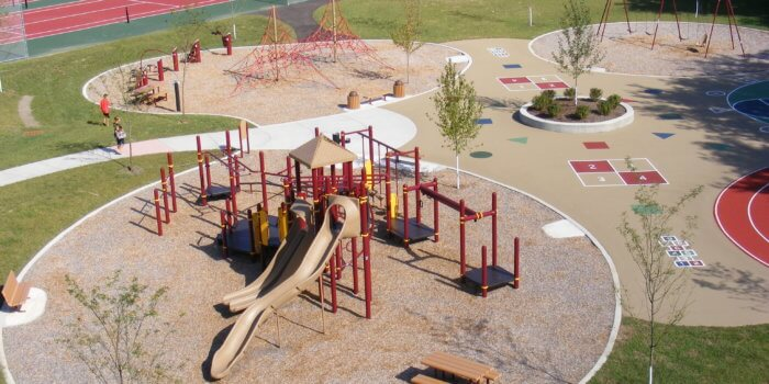Photo of playground structure with multiple decks, slides, and climbers