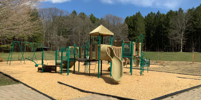 Photo of a playground with multiple decks, slides, and climbers.