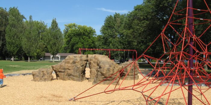 Photo of rock-shaped play structure, swing set, and rope climbing structure