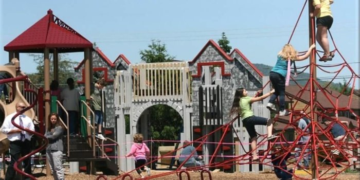 Photo of playground with climbers, slides, and large climbing net.