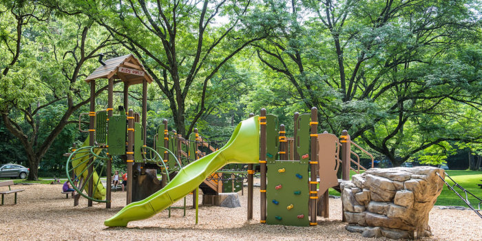 Photo of nature-inspired play structures, with a rock-shaped climber, treehouse roof, and naturally-colored slides, climbers, and panels