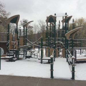 Photo of the snow-covered main play structure consisting of a network of poles and cables