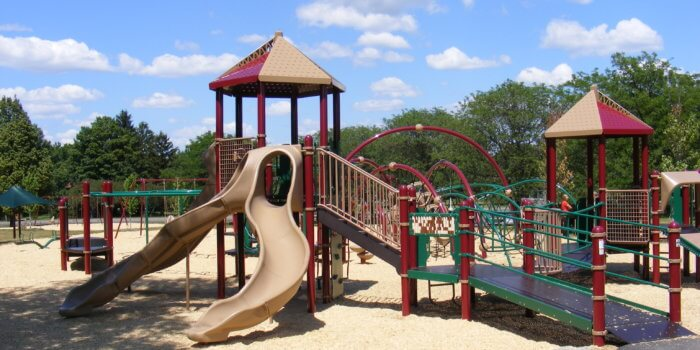 Photo of large playground with wheelchair ramp, slides, swings, and curved climbing structures.