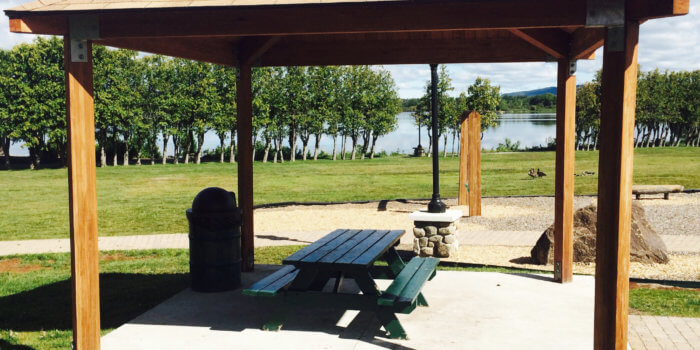 Photo of a wooden pavilion shelter, with a lake and nature-inspired site furnishings visible in the background