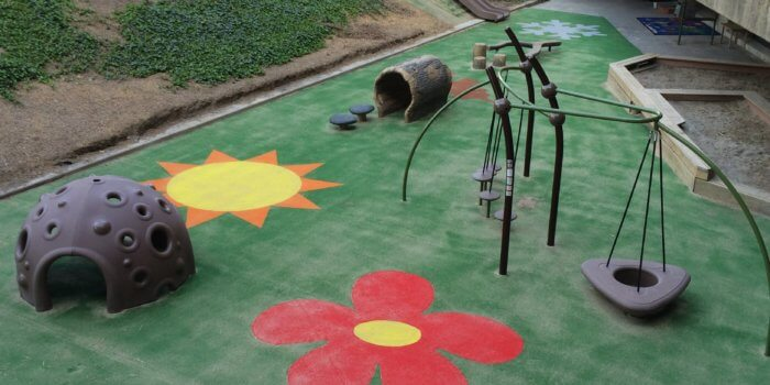Photo of nature inspired playground, with sensory dome, log shaped tunnel and balance beam, and a hill slide, and durable carpeting.