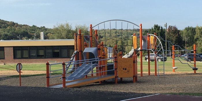 Photo of a playground with multiple decks, play panels, and climbers.