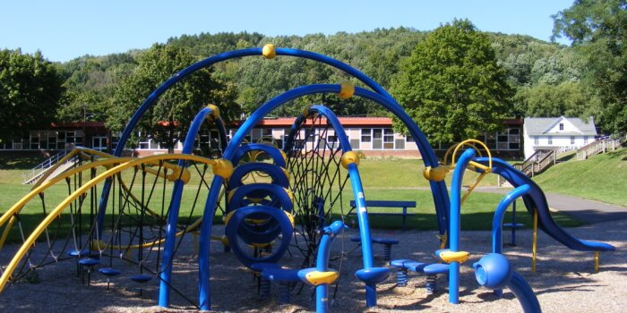 Photo of curved play structure with climbing nets, a slide, and other play components.