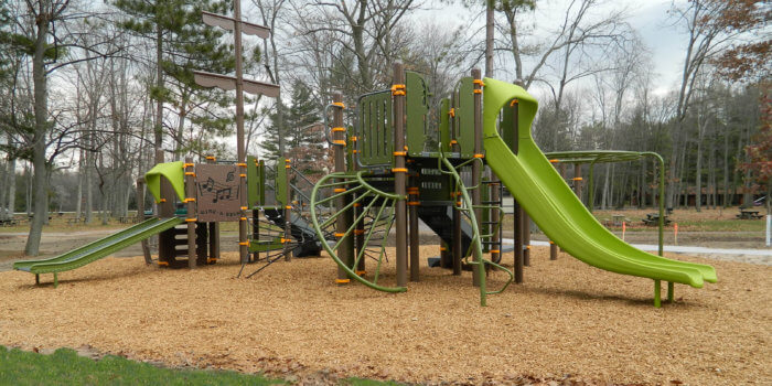 Photo of play structure with multiple decks, climbers, and slides in natural colors