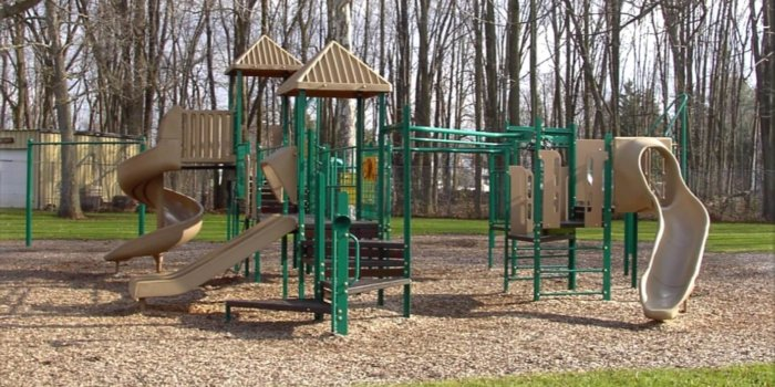 Photo of playground with slides, climbers, decks, and overhead components.