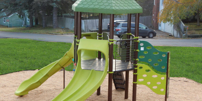 Photo of play structure with slides, roof, and climbers.